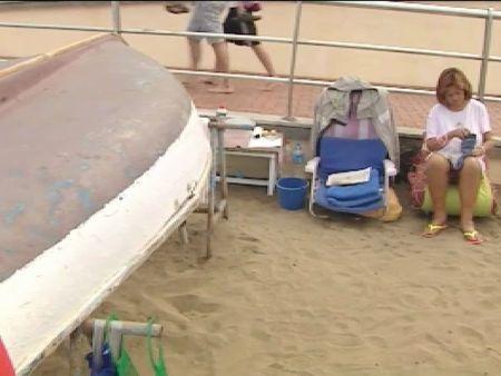 Una pareja vive bajo un barca en la playa de las Canteras en Las Palmas de Gran Canaria